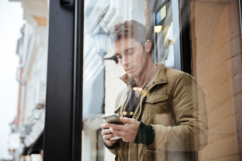Young man walking and chatting by his phone